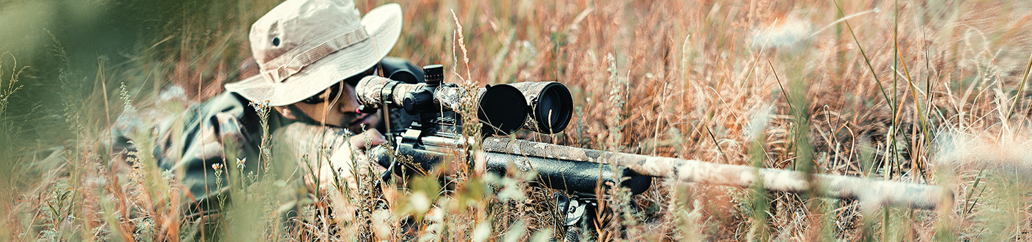 Photo of Man in Tall Grass with Rifle
